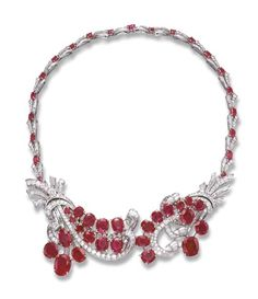 A RUBY AND DIAMOND NECKLACE   The front designed as two circular and baguette-cut diamond foliate scroll motifs, enhanced by oval and cushion-cut ruby detail, joined to the similarly-set backchain, (scroll motifs may also be worn as two brooches)
