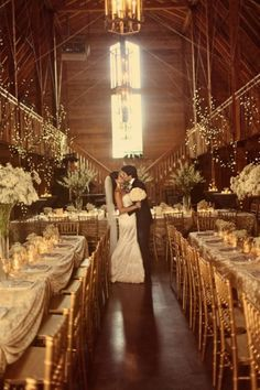 An elegant barn wedding reception with baby's breath centerpieces and twinkle lights.