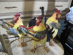 "3 colorful metal roosters with instruments.   We like the call them ""The Henhouse Five.""  When people ask why there are only 3 we explain that we have coyotes.  ;)      ***** These props are available for use by couples holding their weddings at Heart of Rock Farm in Sherwood, Oregon.  To find the top-level board and look at other categories of props (and ideas about how to use them), search for the board called ""Rustic Wedding Props: Heart of Rock Farm"". Wedding Props, Wedding Decorations, Sherwood Oregon, Rustic Wedding, Our Wedding, Hen House, Coyotes, Roosters, Decorative Items"