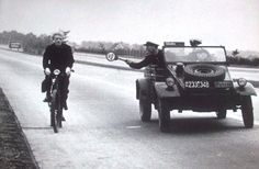 Military police in a VW Type 82 Kubelwagen a trying to stop a suspicious bicyclist