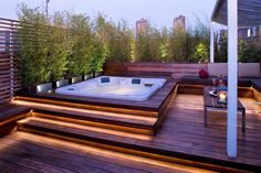 This luxurious hot tub spa is installed in the balcony or terrace patio. The hot tub is all surrounded with the wooden platform, steps and a whole wooden patio sitting area. The planters are inculcated with high green bushes to create a lavish and green natural atmosphere. The couch, benches and coffee table are giving opportunity to enjoy an evening to its fullest.