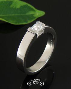 Custom minimalist style 950 platinum mounting to holding a half bezel set 0.7ct emerald cut diamond.
