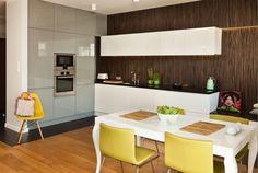 pstrongBiała kuchnia/strong wygląda elegancko na tle hebanowego forniru na ścianie. strongAranżację kuchni/strong ocieplają zielone akcenty dodatków oraz drewno w kuchni. Kuchnia jest nowoczesna, a jednocześnie ciepła i przytulna./p