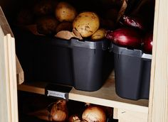 Potatoes and onions are stored in black plastic bins. Veggies like potatoes and onions stay freshest in a cool, dark place, so keep them stored in the cabinet.