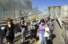 Women wearing dust masks flee across the Brooklyn Bridge from Manhattan to Brooklyn following the collapse of both World Trade Center towers Tuesday, Sept. 11, 2001 in New York. The towers previously loomed tall in the skyline behind.