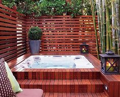 this hot tub, built into a beautiful teak floor in a fenced-in area, designed by Katie Leede, looks sophisticated! #HotTubs