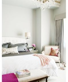Bedroom with grey walls, an ottoman at the foot of the bed, a nightstand with a wall mounted light and an armchair - Home and Garden Design Ideas