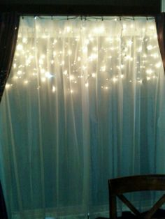 Hang icicle lights behind a window sheer, looks pretty from the inside and outside.