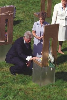 The chairs are memorials for each individual whom died in the bombing. President Clinton stoops down to touch one of the chairs, 4/19/2000. Photograph from the William J. Clinton Presidential Library.