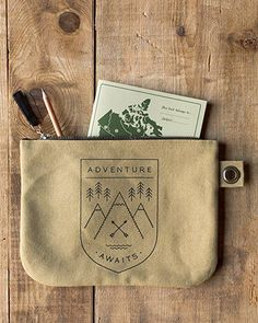 Adventure Awaits Zipper Pouch - A large zipper pouch made from sturdy 100% cotton is perfect for storing drawing supplies, small accessories, travel essentials and more. A metallic zipper keeps contents secure, while a grommet tab adds convenience. A black emblem filled with mountains and evergreens on one side and camping essentials on the other beckons you to get outside. Camping Essentials, Adventure Awaits, Zipper Pouch, Travel Style, Travel Bags, Cosmetic Bag, Craft Supplies, Tote Bag, Wallet