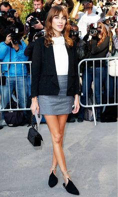 Alexa Chung throws a black jacket over a white blouse tucked into a gray miniskirt with lace-up flats.