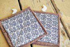 Fabric Hot Pads // Quilted Pot Holders // Black and White Floral Print with Bown Border on Kitchen Pot Holders - Set of Two by QuirkyQuiltress on Etsy https://www.etsy.com/listing/248606592/fabric-hot-pads-quilted-pot-holders