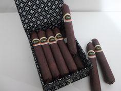 Caixa em cartonagem revestida com tecido 100% algodão com fechamento em elástico Contém dez charutos de chocolate maciço com lacre personalizado.