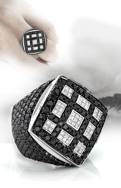 This celebrity 14K Gold White Black Diamond Mens Massive Ring weighs approximately 39 grams and showcases 8.65 carats of dazzling AAA quality round black diamonds and sparkling G/VS quality princess cut white diamonds, each masterfully set in a lustrous gold frame.