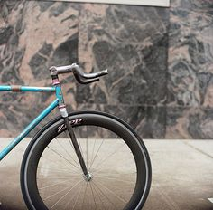 cool, artsy picture - love the texture on the bike and the pattern of the stone material behind it