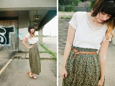 Simple white lace top with belted green flower print skirt and neutral pumps.