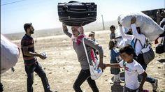 HUIR. Familias kurdos sirios llevan sus pertenencias después de haber cruzado la frontera de Siria, para huir del Estado Islámico que avanzó en esos pueblos. (AFP)