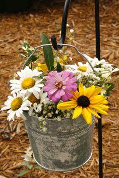 Wildflowers in buckets hanging from shepherd's hooks. Love