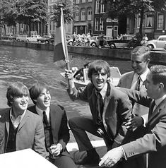 June 6, 1964 The Beatles tour the canals of Amsterdam in a glass-topped tourist boat.