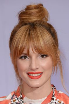 Blunt bangs with wispy edges. Make sure the fringe is shorter in the middle and longer on the edges to create a slimming look.