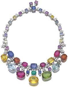 Gem set and diamond necklace, Michele della Valle.     Designed as a series of cushion-shaped and oval gemstones including blue, pink, yellow, green and orange sapphires, pink and blue tourmalines, aquamarines, peridots and emeralds, spaced by brilliant-cut diamonds, the front with a fringe of similar stones, mounted in white and yellow gold, length approximately 410mm, signed della Valle, maker's marks. Via Sotheby's.