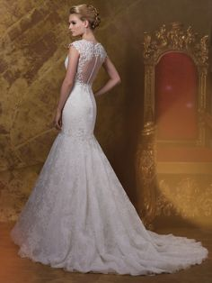 Wedding Dresses 2015 Collection – Allover corded lace on English net, tulle and organza over satin fit and flare wedding dress with hand-beaded lace illusion cap sleeves, plunging deep V-neckline trimmed with beaded appliqués, exaggerated dropped waistline adorned with matching beaded lace appliqués, elegant low back illusion and lace keyhole bodice finished with covered button closures spilling down to dropped waist, softly gathered skirt with scalloped hemline trailing into chapel length…