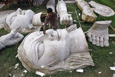 An artisan in Kolkata sandpapers an idol of the Hindu goddess Durga before applying paint on it.