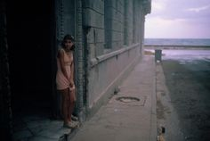 Magnum Photos. David Alan Harvey CUBA. Havana. 1998. A young woman stands in a doorway near the Malecon, Havana's seawall, at dawn.