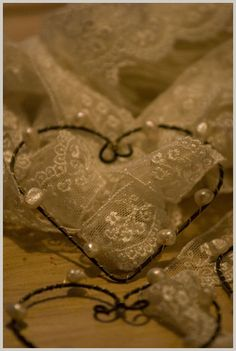 Seeing a twisted wire heart with pearls, strips of appliqued lace, love the inward looped curl at the top of lower heart, these are very pretty!