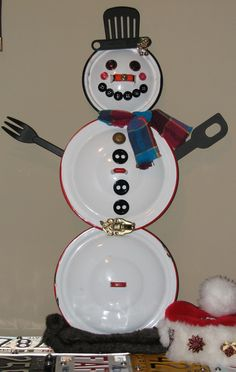 Old enamel pot lid snowman with spatula hat, buttons and belt buckle.