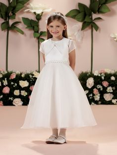 Two-piece satin and organza dress set, sleeveless tea-length A-line dress features an organza overlay bodice accented with a rosette and pearl trim at waist, double layer organza overlay skirt with built-in crinoline, organza short sleeve cropped jacket with frog closure, ideal as a First Communion dressor flower girl dress.Sizes: 2 - 14,8 ½ - 14 ½