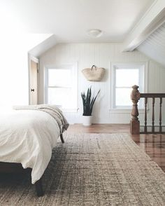 simple, minimalist bedroom with snake plant, white bedding, and natural jute rug.
