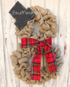 The Snowman Burlap Wreath accented with a beautiful red tartan plaid scarf and a wooden tophat! The perfect addition to your home this winter
