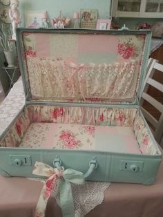 Love the blue paint and the rosebud fabric inside this shabby and vintage suitcase.