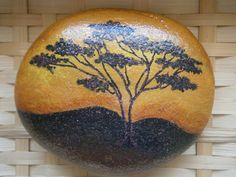 Painted rock Africa. Inspired by a photograph of a sunset in Africa. Acrylic paint on a river rock. Covered with glitters. Size approximately 6