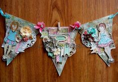 Julie Nutting has created a stunning banner using her sweet Mixed Media Doll stamps, along with Prima canvas, flowers and more!