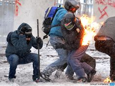 UKRAINE, Kiev : Protesters clash with the police in the center of Kiev on January 22, 2014. Ukrainian police on Wednesday stormed protesters' barricades in Kiev as violent clashes erupted and activists said that one person had been shot dead by the security forces. Total of two activists shot dead during clashing.  AFP PHOTO/ SERGEI SUPINSKY