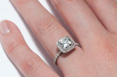 Charmypoo's platinum ring features a 1.52 carat G VS1 modern cushion cut diamond surrounded by a pave halo.