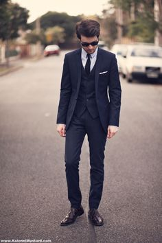 Sleak 60's look, with English influences (note wide spread of bottom hem on vest, cut shoulders). But the slender tie and straight legs are very chique.