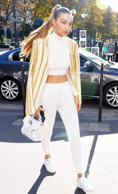 2015: Gigi Hadid wears a high-neck crop top, sweatpants, a Proenza Schouler bag, sneakers, and a gold and white jacket