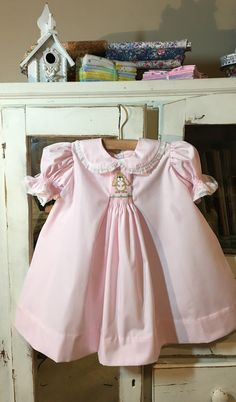 af65680cf This vintage inspired pink broadcloth smocked Apron dress features a  smocked rabbit. The collars and