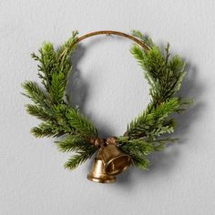 Whether you're looking for a new wreath for the holidays or want to have fresh-looking greenery in your home throughout the year, the Artificial Pine Wreath with Bell from Hearth & Hand with Magnolia™ is sure to hit the mark. A beautiful circle of faux pine branches and artificial juniper berries gets just a hint of glimmer from two antiqued gold bells hanging in the center. This faux wreath is the perfect way to decorate your home with a touch of nature.<br><br>C...