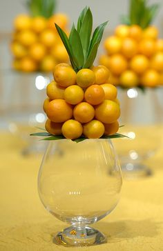 Attach lemons to cone or egg shape or real pineapple. Top & bottom have 6 lemons. Set on magnolia leaves. The empty vase could also contain a floating flower