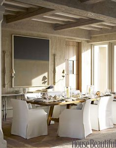 Don't Be Afraid to Mix Design Styles, rustic, slipcovered dining chairs, white room, rustic dining table, simple artwork