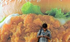 A man checks his phone in front of an advert for a burger in Mumbai.