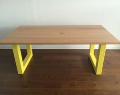 Modern wooden table with coloured stainless steel legs