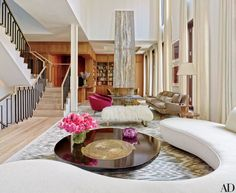 A travertine-clad fireplace punctuates the far end of the living room; the carpet is by Luke Irwin.
