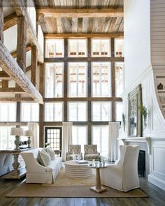 Love the loft-like windows and ceilings, combined with the old log cabin elements, finished off with traditional classy white furniture. What a great blend of styles!