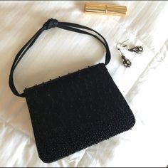 Black beaded evening bag Need a little bag to keep your lipstick, phone, ID and other touch up accessories contained? This pretty satin beaded evening bag is it. Choose either the small wristlet length handle or hip-length strap for carrying. Magnetic snap closure. Solid base. Great condition; only used twice. Clean interior with small ID-sized pocket. Perfect bag for prom, formal dance, or other dressy/black tie occasion. Questions, bundles and offers welcome. Bags Mini Bags