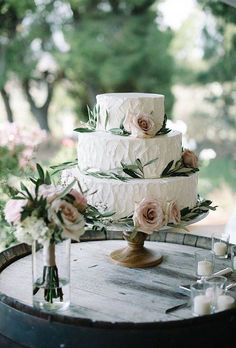 A classic floral wedding cake made rustic with decorative eucalyptus leaves by Edelweiss Bakery.